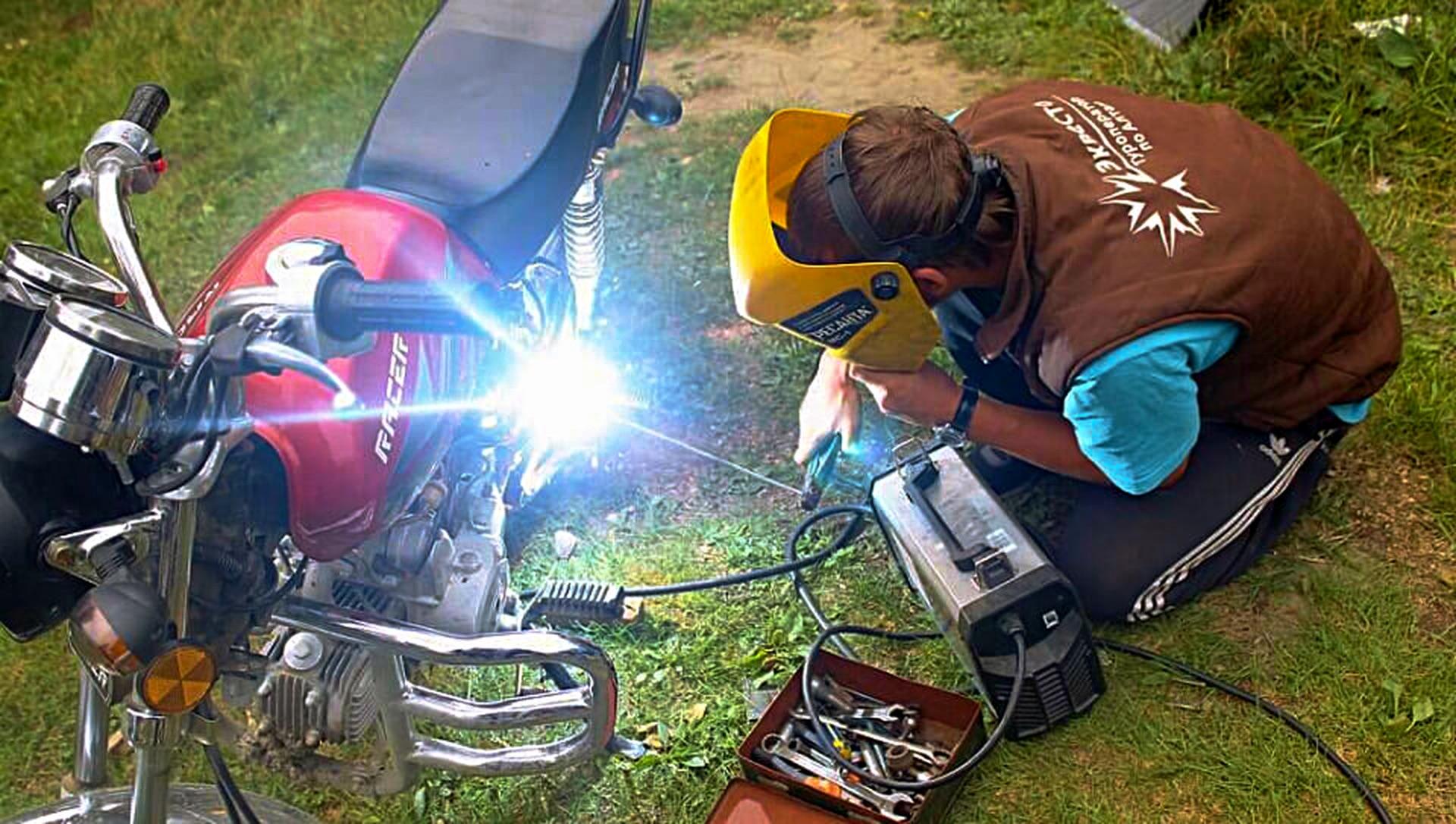 Гид на участке пути — он же местный алтаец — за починкой мотоцикла